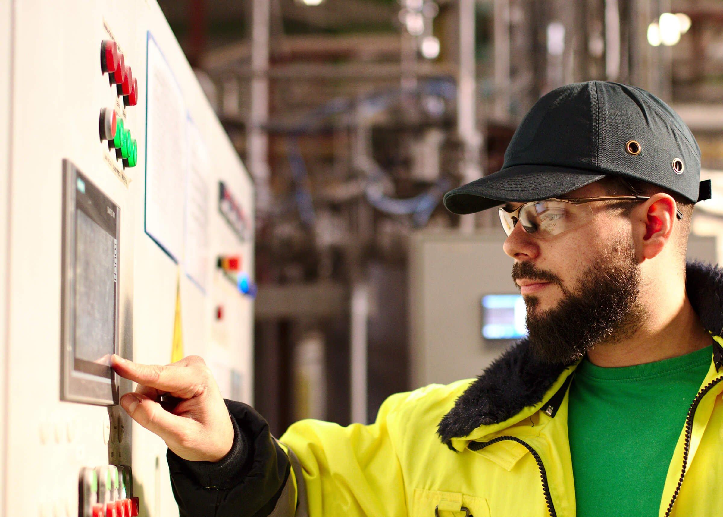 opérateur avec casquette noire et veste jaune devant un panneau de commande