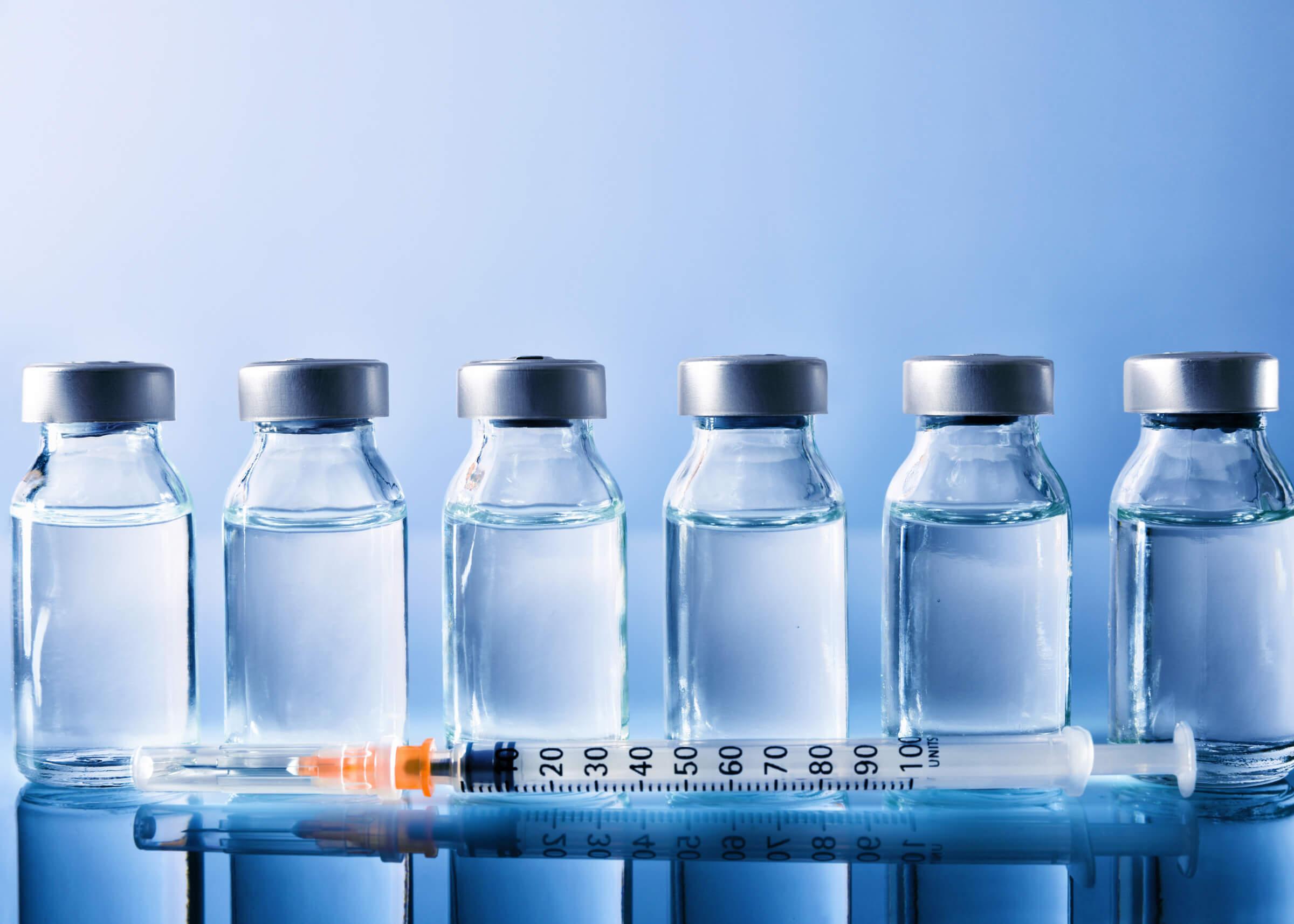 seringue devant 6 fioles de médicaments