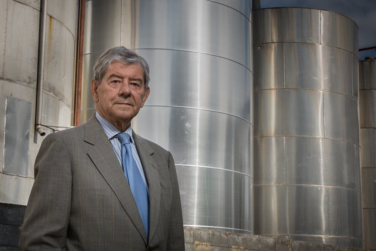 Philippe Delaunoix in costume in front of stainless steel tanks