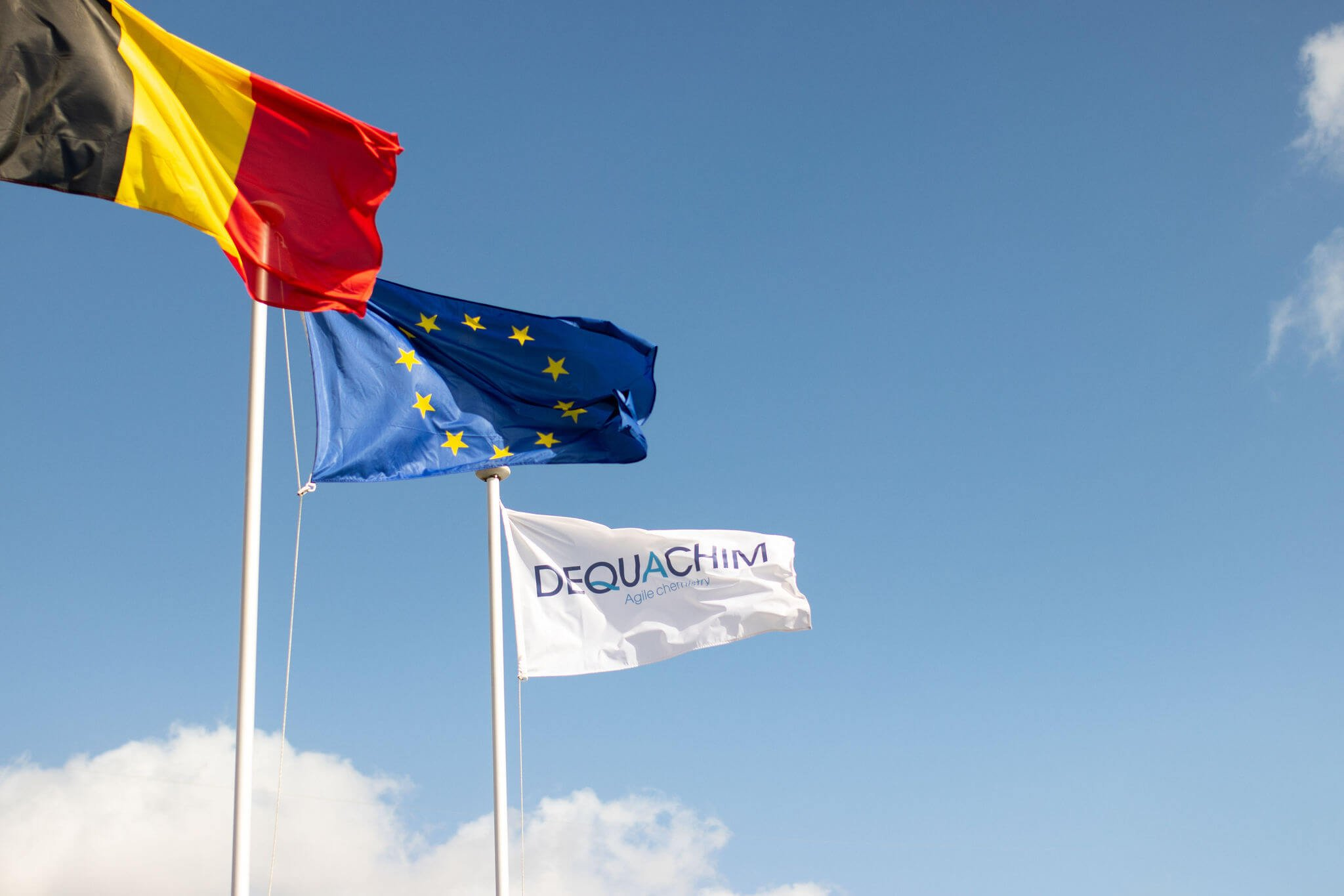 Belgian, European and Dequachim flags on blue sky background